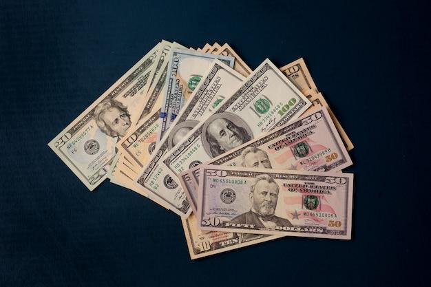 어두운 테이블에 흩어져있는 달러