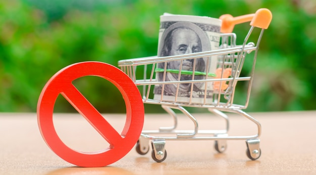 Dollars in a shopping cart and sign of prohibition