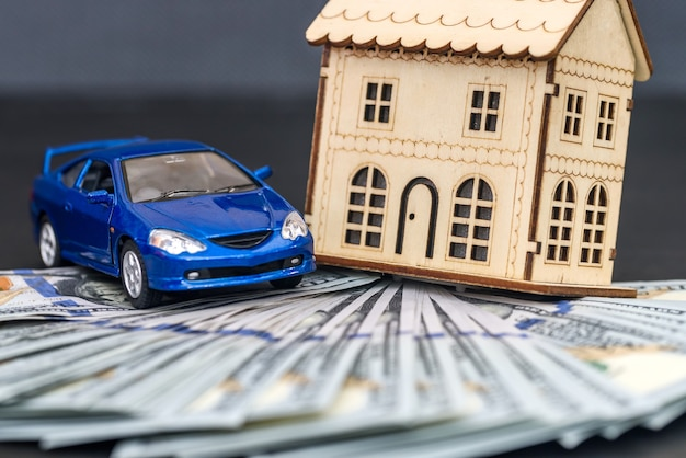 On dollars there is model wooden house and toy car