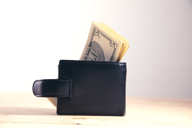 Dollars and wallet on gray surface
