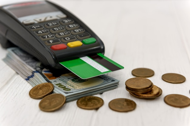 Dollars with coins and banking terminal with credit card