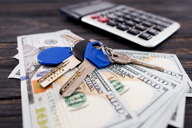 Dollars with keys to the apartment and calculator. close-up. home purchase, mortgage or loan concept
