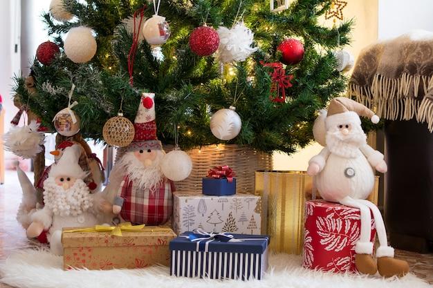 クリスマスツリーの下の白いじゅうたんに人形、ギフト、サプライズ。