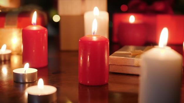 크리스마스 선물이 있는 많은 출현 양초와 상자의 돌리 4k 푸티지와 나무 테이블에 있는 선물. 크리스마스 또는 새해를 위한 완벽한 배경 또는 배경