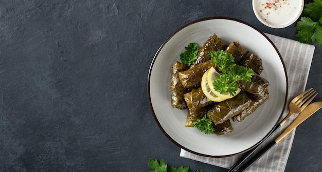 暗い背景のドルマ。伝統的な白人料理、トルコ料理、ギリシャ料理、上面図、テキストの場所