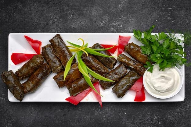 Долма на белой прямоугольной тарелке, с зеленью, сметаной и болгарским перцем, на темном фоне