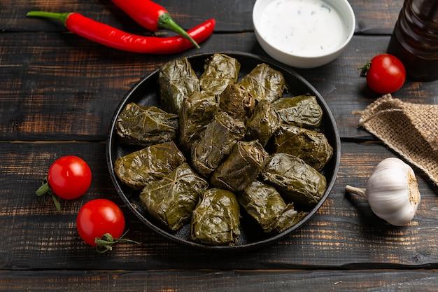 ドルマまたはトルマまたはサルマは、木製の背景にご飯と肉をブドウの葉に詰めました。伝統的な白人料理、オスマン料理、トルコ料理、ギリシャ料理