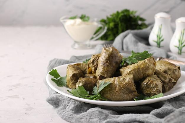 Долма - фаршированные виноградные листья с рисом и мясом на белой тарелке на светло-сером фоне. традиционная кавказская, греческая, османская и турецкая кухня, крупным планом
