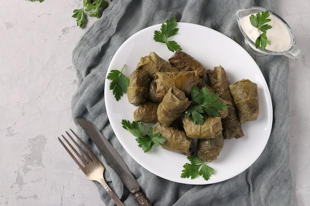 Долма - фаршированные виноградные листья с рисом и мясом на белой тарелке на светло-сером