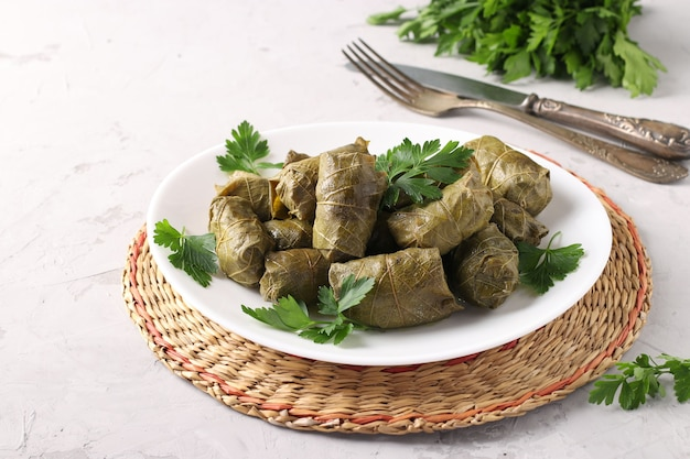 ドルマ-ライトグレーの白いプレートにご飯と肉を詰めたブドウの葉。
