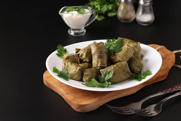 ドルマ-木の板の白い皿にご飯と肉を詰めたブドウの葉。伝統的なコーカサス料理、ギリシャ料理、オスマン帝国、トルコ料理、クローズアップ