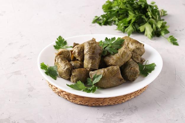Долма, фаршированные виноградные листья с рисом и мясом на белой тарелке