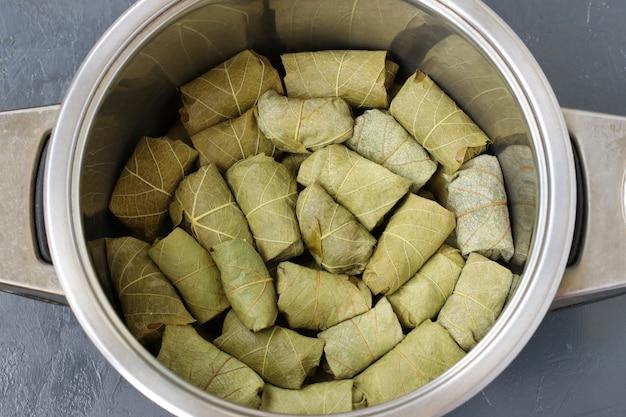 Долма, фаршированные виноградные листья с рисом и мясом, уложенные слоями на сковороде