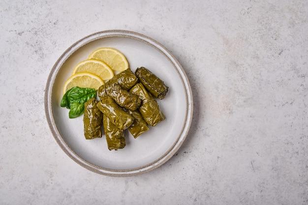 ドルマは、ライトプレートの上面図に米肉パセリとレモンを詰めたブドウの葉