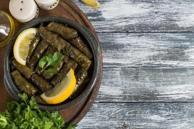 ドルマ-青い木製の背景に詰められたギリシャワインの葉(ドルマデ)