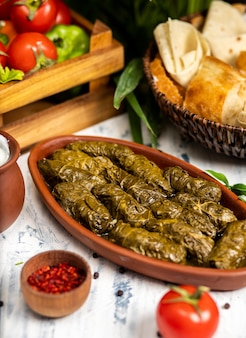 Dolma (tolma, sarma) - stuffed grape leaves with rice and meat. on kitchen table with yogurt, bread, vegetables. traditional caucasian, ottoman, turkish and greek cuisine