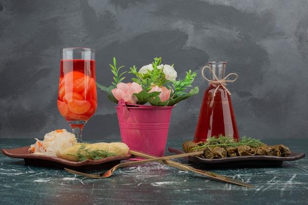 Dolma con vetro e bottiglia di succo sulla parete di marmo