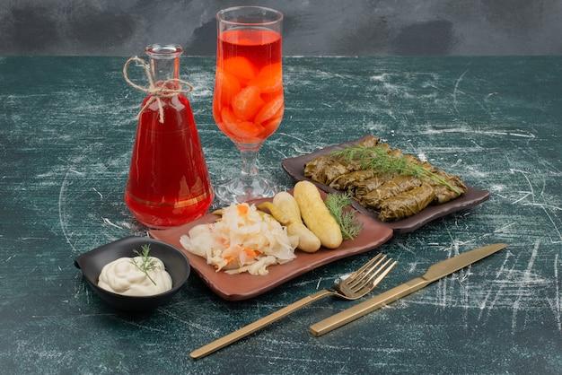 Dolma con un bicchiere di succo di frutta e panna acida sulla parete di marmo.