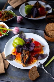 Dolma with minced meat tomatoes green bell pepper and purple leaves inside white plate