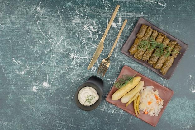 사워 크림과 소금 양배추와 오이 접시를 곁들인 돌마.