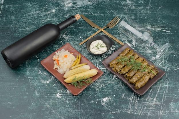 Dolma con panna acida e piatto di cavolo cappuccio e cetriolo.
