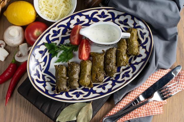 伝統的なウズベキスタンの皿に野菜とディルソースを添えたドルマ