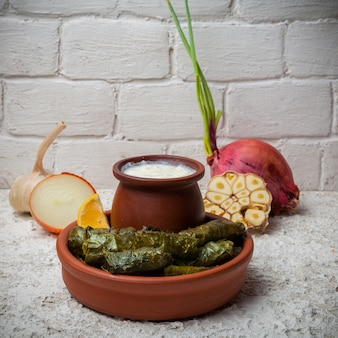 Dolma with yogurt and onion and garlic in clay dishes