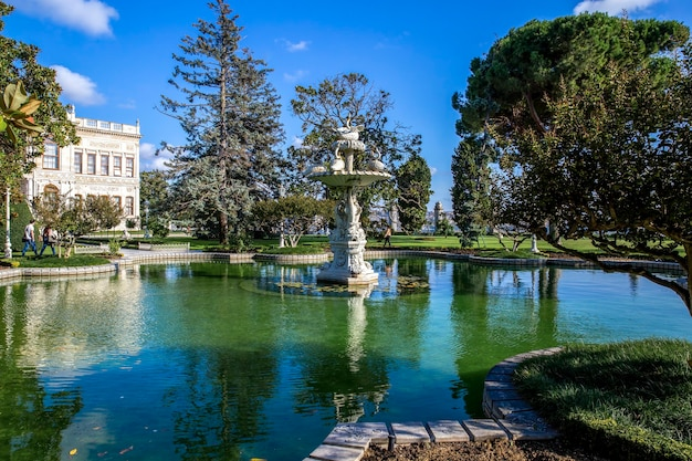 Dolmabahce palace gardens with a lot of greenery, fountain and pond with water, turkey