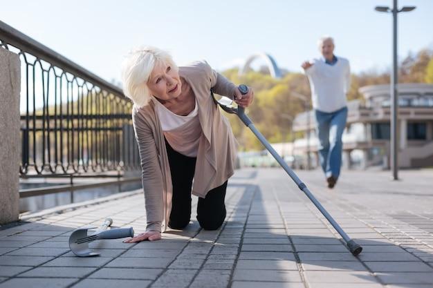 老人が彼女を助けようと急いでいる間、胃の痛みを感じて松葉杖を落としている悲惨な無力な病気の女性
