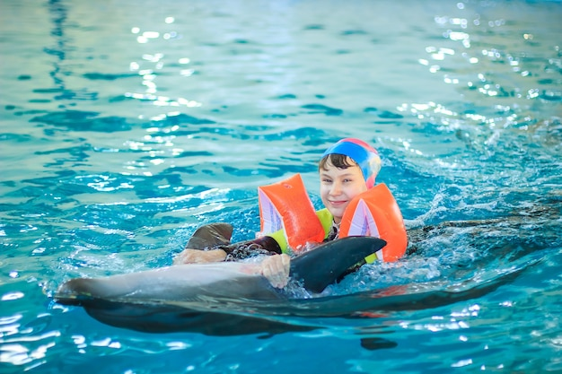 Dolphin therapy. happy little girl swimming with dolphins in dolphinarium. swimming, bathing and communication with dolphins. treatment of children by means of dolphins. concept people and dolphins.
