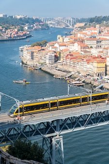 Поезд метро, пересекающий мост dom luis i в порту, португалия