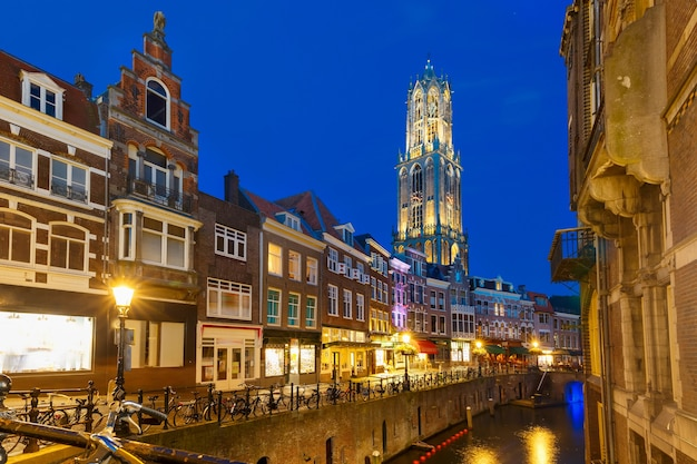 Dom tower bridge and canal oudegracht in the night colorful illuminations in the blue hour utrecht