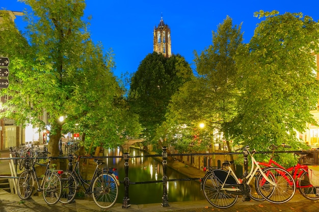 Dom tower and bridge with bikes over canal oudegracht in the night colorful illuminations