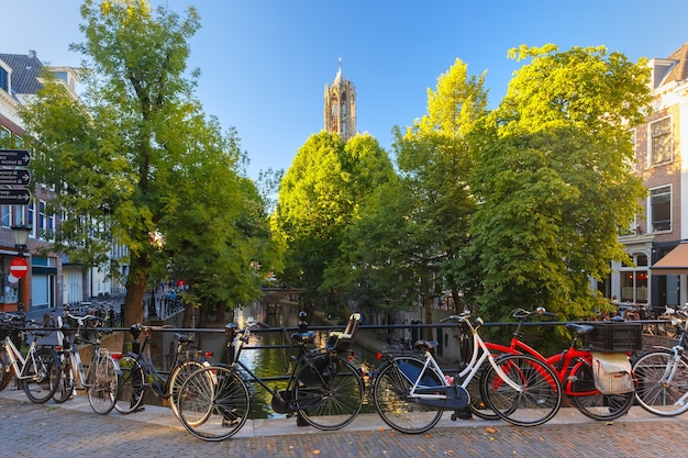 Dom tower, canal and bridge with bikes in the sunny evening, utrecht, netherlands