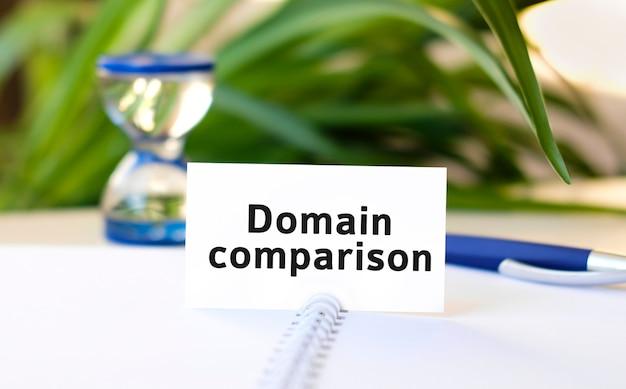 Текст бизнес-концепции seo сравнения доменов на белом блокноте и песочных часах, синяя ручка, зеленые цветы