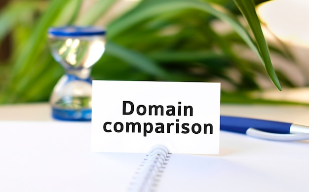 Domain comparison seo business concept text on a white notebook and hourglass, blue pen, green flowers