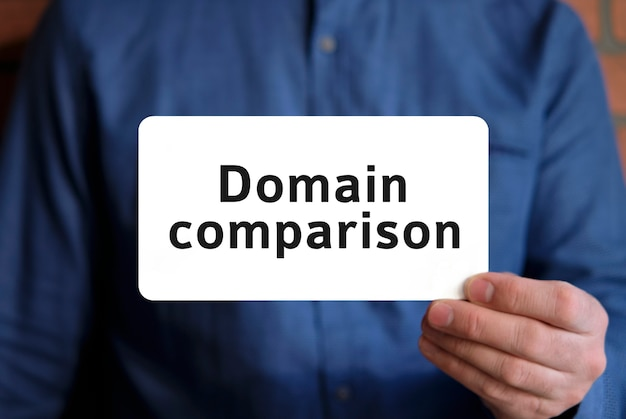 Domain comparison text on a white sign in the hand of a man in a blue shirt