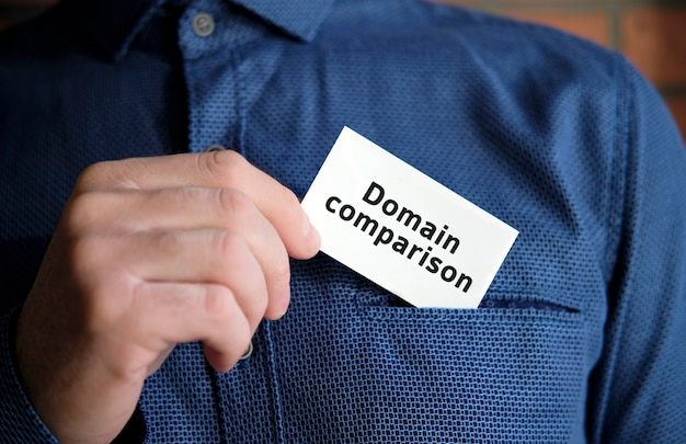 Domain comparison text on a white sign in the hand of a man in shirt