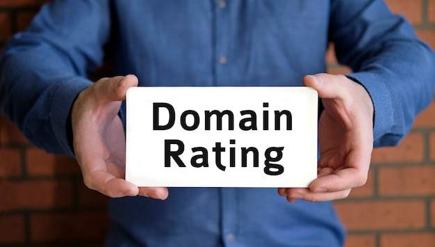 Domain rating - seo concept in the hands of a young man in a blue shirt