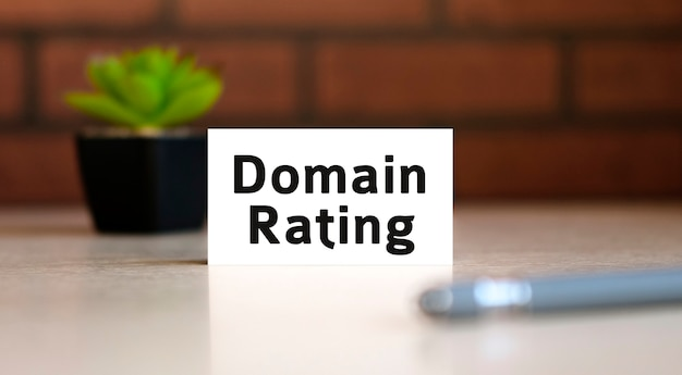 Domain rating text of business concept on white list and with pen and a black pot with a flower behind