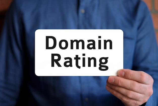 Domain rating text on a white sign in the hand of a man in a blue shirt