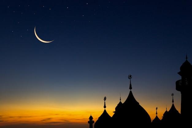 イスラム教徒のためのイスラム教の夕暮れの空と三日月の空のドームモスクのシルエット