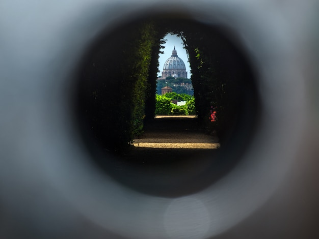 The dome of saint peters basilica seen through the famous keyhole at rome
