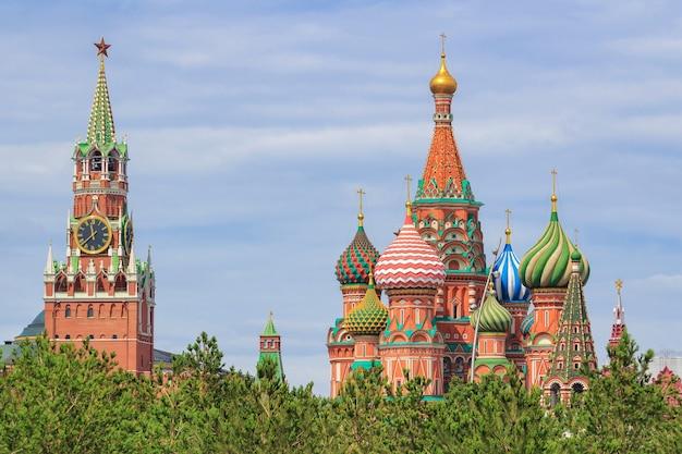 Купола собора василия блаженного на красной площади и спасской башни московского кремля на фоне зеленых деревьев и облачного неба в летний день