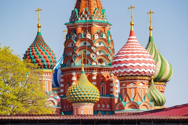 Купола собора василия блаженного на красной площади в москве против голубого неба и зеленых деревьев