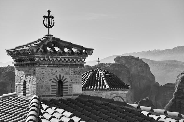 ギリシャのヴァルラーム正教会とメテオラ岩の十字架が背景にあるドーム。黒と白のギリシャの風景
