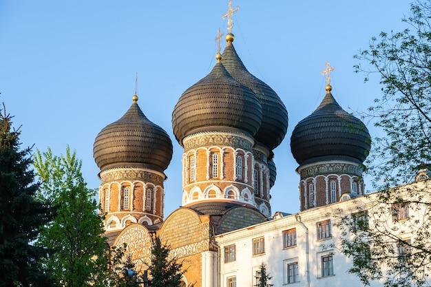 Купола с золотыми крестами покровского собора над голубым небом в свете заходящего солнца