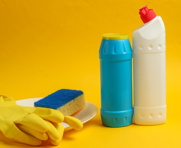 Domestic accessories for washing dishes. detergent bottles, sponge, gloves and white plate on yellow background