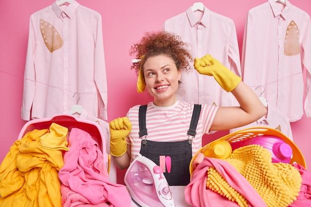 家事と洗濯のコンセプト。ポジティブな巻き毛の女性は、家事をするのに忙しい洗濯かごの近くで腕を上げたポーズで踊ります。家事を終えて満足した幸せな家政婦