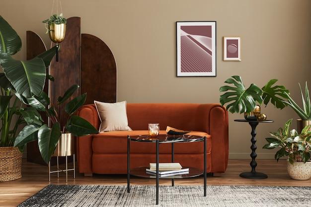 Домашний интерьер гостиной с дизайнерским диваном, рамами, множеством растений, журнальным столиком, ширмой и элегантными личными аксессуарами в современном домашнем декоре.